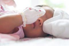 Fermez-vous vers le haut du visage nouveau-né avec la lumière du soleil Une partie de visage Nouveau-né dort Photographie stock