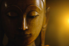 Fermez-vous vers le haut du visage sur la statue de tête de Bouddha avec l'effet de la lumière Photos stock