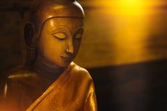 Fermez-vous vers le haut du visage sur la statue de tête de Bouddha avec l'effet de la lumière Photographie stock libre de droits