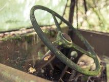 Fermez-vous vers le haut du volant sur le camion abandonné dans les bois avec des toiles d'araignée Photo stock