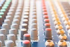 Fermez-vous vers le haut du volume ajustant des boutons vieux sur le contrôleur audio de mélangeur dans la salle de commande photographie stock