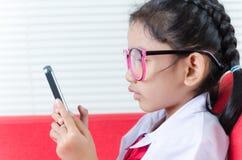 Fermez-vous vers le haut fille asiatique de tir de la petite dans l'uniforme d'étudiant utilisant le smartph image stock