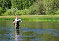 Fermi del pescatore della pesca con la mosca del cavedano nel fiume di Chusovaya Immagine Stock