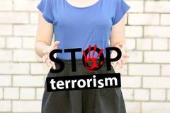 Fermi il concetto del terrorismo ragazza su un muro di mattoni Fotografia Stock