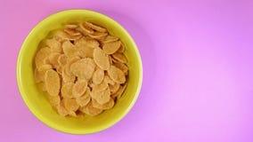 Fermi il moto della ciotola gialla con cereale sul fondo di colore stock footage
