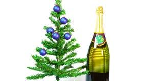 Fermi il moto, le palle del ` s del nuovo anno su un albero del nuovo anno e una bottiglia enorme di vino spumante video d archivio