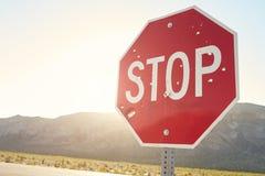Fermi il segnale stradale con i fori di pallottola sulla strada campestre Immagine Stock
