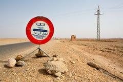 Fermi il segno della polizia contro un cielo blu sulla strada Immagini Stock Libere da Diritti