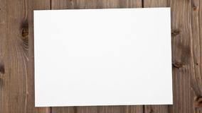 Fermi l'animazione di moto: Non imballato foglio bianco del modello della carta su fondo di legno archivi video