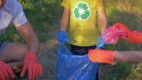 Fermi l'inquinamento, il bambino volontario aiuta i genitori a raccogliere i rifiuti nella borsa di rifiuti mentre libera la natu video d archivio