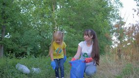Fermi l'inquinamento, la piccola figlia aiuta la madre in guanti di gomma a raccogliere i rifiuti del polietilene e della plastic video d archivio