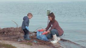 Fermi l'inquinamento, volontari della donna con la costa sporca pulita del ragazzo del piccolo bambino da rifiuti di plastica su  video d archivio