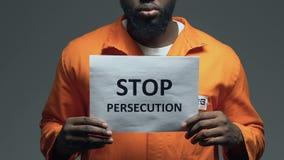Fermi la frase di persecuzione su cartone in mani del prigioniero afroamericano, assalto archivi video