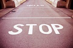 Fermi scritto su asfalto rosso Fotografia Stock