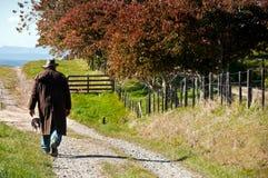Fermier marchant à sa ferme Photographie stock libre de droits