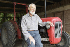 Fermier organique s'asseyant par Vintage Tractor images stock