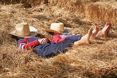 Fermiers en sommeil dans le foin images stock
