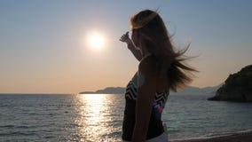 Fermo femminile The Sun delle mani di piacere nel cielo che sta sul mare della costa Fotografia Stock