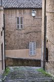 Fermo Marches, Italy. Historic buildings along an old typical alley Stock Photos