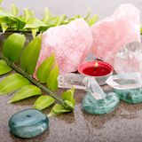 Fern leaf with healing crystals and red candle Stock Photos
