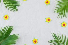 Fern leaves and yellow paper flowers. On muslin fabric with copy space Royalty Free Stock Photo