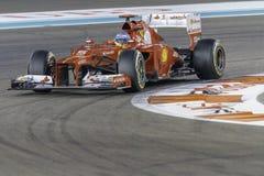 Fernando Alonso que arrincona un coche de Ferrari F1 en el circuito de carreras Abu Dhabi del puerto deportivo de Yas Fotos de archivo
