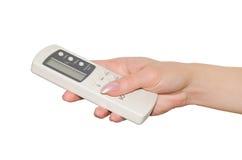 Fernbedienung für Klimaanlage in einer weiblichen Hand. Lizenzfreies Stockfoto