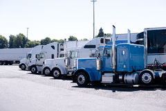 Fernfahrerrastplatz mit Reihe von großen LKWs der Anlagen halb Stockbilder