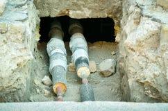 Fernheizungsrohrleitungen schlossen an ein Wohngebäude durch die Grube in der Grundlagenbasis an Stockfotos