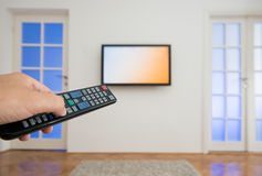 Fernsehen Fernsteuerungs halten mit einem Fernsehen als Hintergrund Lizenzfreies Stockfoto
