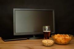 Fernsehen und Computer mit ungesundem Snack auf der Tabelle lokalisiert auf Schwarzem Lizenzfreie Stockfotografie