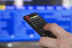 Fernsehfernbedienung und -hand Stockbild