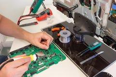 Fernsehreparatur in dem Service-Center, Ingenieur, der elektronische Bauelemente lötet Lizenzfreie Stockfotos