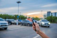 Fernsteuerungsschlüsselauto in der Hand im Parkplatz im Freien am Abend Lizenzfreies Stockbild