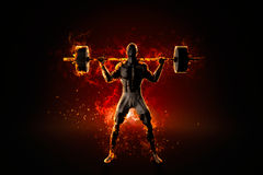 Ferocious flaming bodybuilder with barbell.  Stock Photo