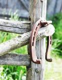 Ferradura oxidada antiga fixada em pregos na superfície de madeira velha Foto de Stock