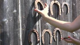 Ferradura velha do cair fêmea da mão na fileira na parede do prego exterior 4K vídeos de arquivo