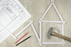 Ferramenta branca do medidor que forma uma casa e que projeta ferramentas no woode Foto de Stock