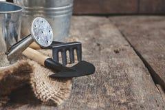Ferramenta de jardim, pá, ancinho, lata molhando, cubeta, saco em um de madeira Imagens de Stock