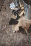 Ferramenta de jardim, pá, ancinho, lata molhando, cubeta, saco em um de madeira Fotos de Stock Royalty Free