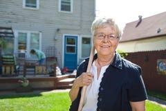 Ferramenta de jardinagem sênior da terra arrendada da mulher Fotografia de Stock