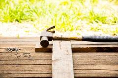 Ferramenta do artesão do fundo com martelo velho e pregos pequenos no fundo de madeira e no estilo country exterior da vista Foto de Stock Royalty Free