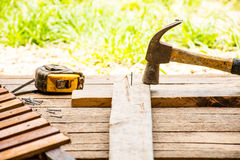 Ferramenta do artesão do fundo com o martelo velho com fita métrica e pregos pequenos no fundo de madeira e na vista exterior Imagens de Stock Royalty Free