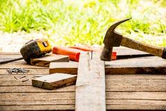 A ferramenta do artesão do fundo tal como o martelo velho com fita métrica e os pregos pequenos e viu com luva e vista exterior F Foto de Stock