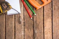 A ferramenta do artesão do fundo tem a serra e a fita métrica e o lápis e o caderno da madeira No fundo de madeira Tela para o ca Fotos de Stock