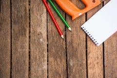 A ferramenta do artesão do fundo tem a serra e o lápis e o caderno da madeira No fundo de madeira Tela para o carpinteiro Fotografia de Stock Royalty Free