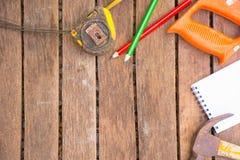 A ferramenta do artesão do fundo tem a serra e o martelo e a fita métrica e o caderno No fundo de madeira Tela para o carpinteiro Imagens de Stock Royalty Free