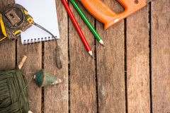 A ferramenta do artesão do fundo tem a serra e o martelo e a fita métrica e o caderno No fundo de madeira Tela para o carpinteiro Imagem de Stock