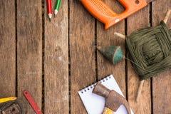 A ferramenta do artesão do fundo tem a serra e o martelo e prumo a prumo e fita métrica e caderno No fundo de madeira Foto de Stock Royalty Free