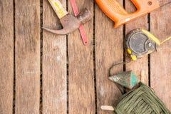 A ferramenta do artesão do fundo tem a serra e o martelo e prumo a prumo e fita métrica e caderno No fundo de madeira Imagens de Stock Royalty Free